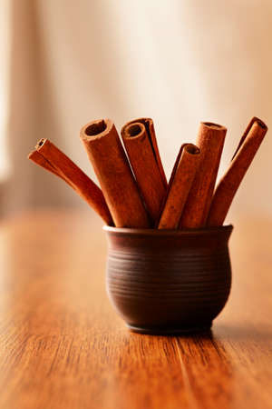 stick of cinnamon: Collection of natural stick cinnamon , a spicy tree bark used in cooking, standing upright in a pottery container on a wooden table with copyspace