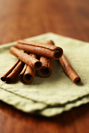 flavouring: Spicy fresh cinnamon sticks used as a seasoning and flavouring in cooking lying on a napkin with the rolled end of the bark facing the camera Stock Photo