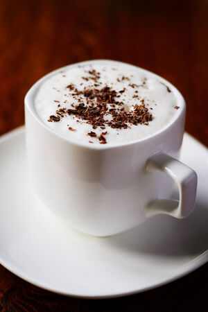 addictive drinking: Sweet coffee with cream and chocolate flakes, in an elegant white cup with saucer, on wooden table