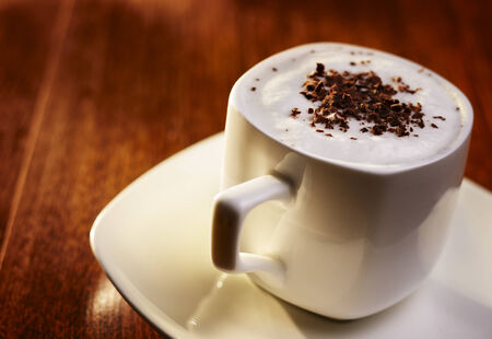 grated: Sweet coffee with cream and chocolate flakes, in an elegant white cup with saucer, on wooden table