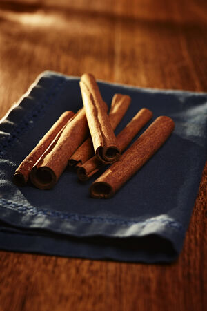 stick of cinnamon: Pile of stick cinnamon on a napkin viewed from the end to show the rolled bark on a wooden table with shallow dof Stock Photo