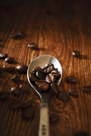 addictive drinking: Close-up of a silver teaspoon filled with roasted cofee beans on a wooden table