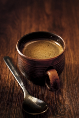stimulant: Cup of freshly brewed hot espresso coffee in a brown pottery mug served on a wooden table with a spoon for a refreshing morning stimulant