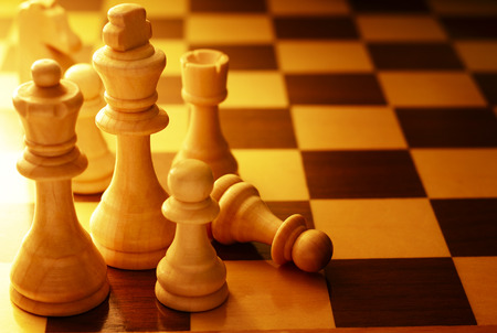 chessboard: Team of chess pieces on a chessboard with focus to a fallen pawn and copyspace, high angle view