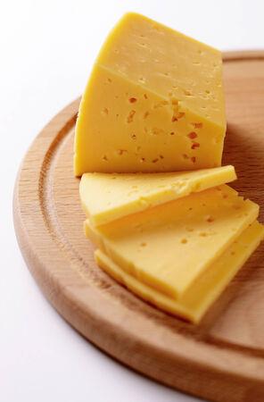 tabla de quesos: Bloque del queso cortado en rodajas o partes de una tabla de quesos de madera, listo para ser servido como aperitivo o postre o utilizarse como ingrediente de cocina