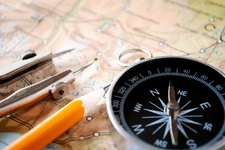 Conceptual image of a magnetic compass and pencil lying on a map for plotting a journey, geocaching or orienteering where it is used as a navigational instrument