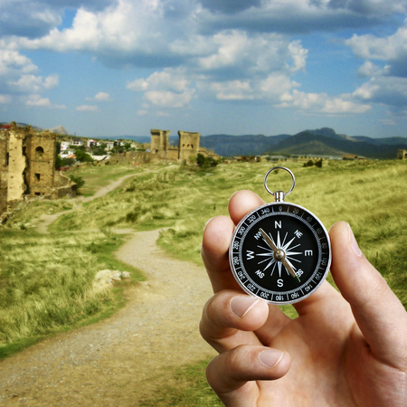 castles needle: Conceptual image of the hand of a man using a compass to navigate and find the direction while sightseeing abroad with the ruins of an ancient castle in the background