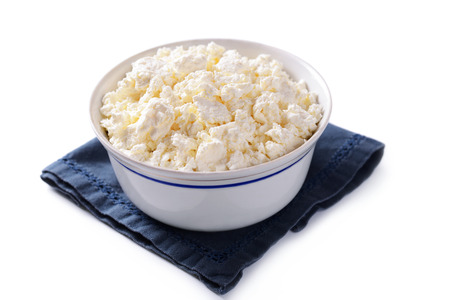 crumbly: Bowl of soft crumbly cottage cheese made from the curds of skim milk served in a blue bowl