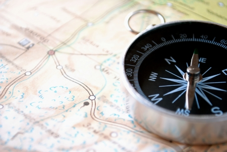 Handheld compass lying on a map showing the needle and cardinal points of north, south, east and west to aid in magnetic navigation to plot a route or direction to a specific destination