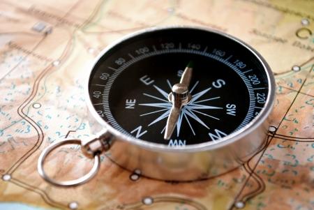 ハンドヘルド コンパスの針と北、南の基本的なポイントを示す地図に東と西ルートや特定の宛先への方向をプロット磁気ナビゲーションを支援する