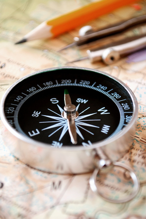 orienteering: Conceptual image of a magnetic compass and pencil lying on a map for plotting a journey, geocaching or orienteering where it is used as a navigational instrument