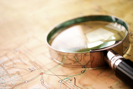 clues: Handheld magnifying glass lying on a map conceptual of search, discovery , planning and exploration Stock Photo
