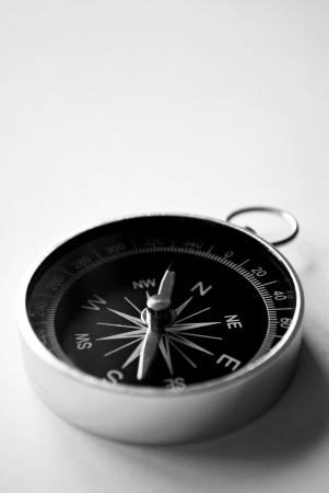 opportunity discovery: Close up view of a magnetic handheld compass with copyspace showing the needle, compass rose and cardinal points conceptual of planning, navigation, discovery, travel and strategy Stock Photo