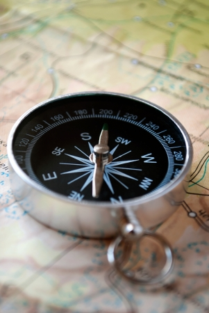 handheld: Handheld compass lying on a map showing the needle and cardinal points of north, south, east and west to aid in magnetic navigation to plot a route or direction to a specific destination