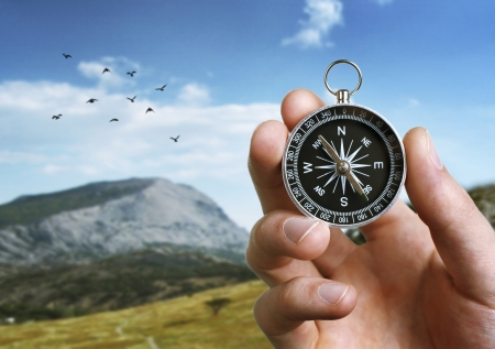 orientation: Close up of the hand of a man holding a magnetic compass over a landscape view as he uses it to navigate when exploring or travelling in the countryside Stock Photo