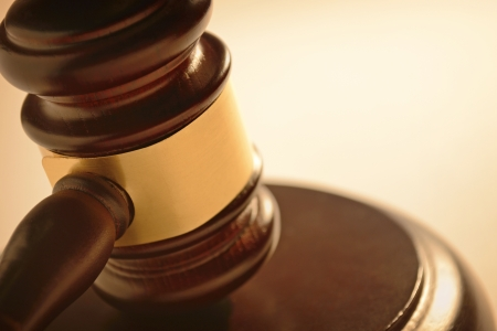 sentencing: Close up of a wooden judge or auctioneers gavel with a brass band on a wooden base for delivering judgement