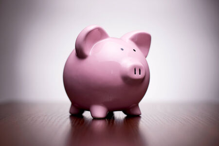Small ceramic pink piggy bank with vignetting, conceptual of money, finances, retirement and saving for your dreams and goals Stock Photo