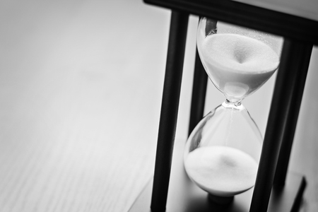 timekeeping: High angle close up view of sand running through an hour glass or egg timer measuring the passing time and counting down to a deadline Stock Photo
