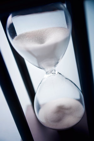 running out of time: High angle close up view of sand running through an hour glass or egg timer measuring the passing time and counting down to a deadline Stock Photo