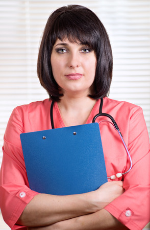 Beautiful young woman doctor holding a clipboard with patient records pausing on her ward rounds to look at the camera with a serious expression photo