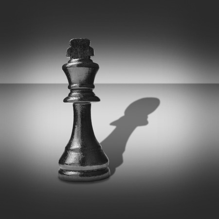 pawn to king: Black and white image of a king chess piece casting a shadow belonging to a pawn into a central highlight surrounded by vignetting Stock Photo