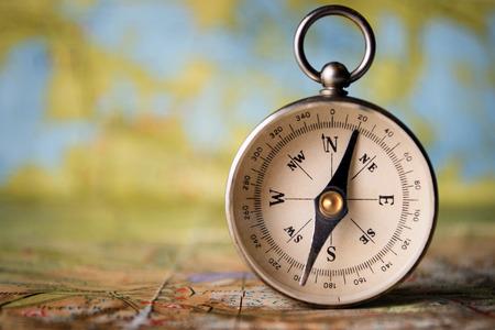 Magnetisch kompas rechtop op een wereldkaart conceptuele van de wereldwijde reizen, toerisme en exploratie, met copyspace