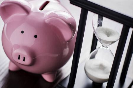 running out of time: Pink ceramic piggy bank with an hour glass, conceptual of time running out to save for your retirement, a nest egg or to meet your dreams