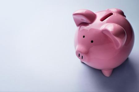 Copyspace와 회색 배경 위에 그것의 뒷면에 동전 슬롯에 초점을 맞춘 핑크 세라믹 돼지 저금통의 높은 각도보기와 개념 금융 이미지 스톡 콘텐츠