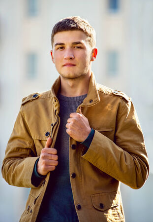 lapels: Young man with a speculative thoughtful expression standing holding the lapels of his jacket looking down at the camera with a watchful gaze Stock Photo