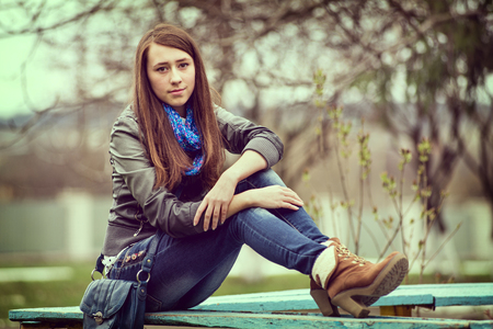 girl sit: Attractive young girl enjoying a quiet moment on a wooden bench sitting with her feet up in fashionable jeans and high heeled boots smiling at the camera Stock Photo