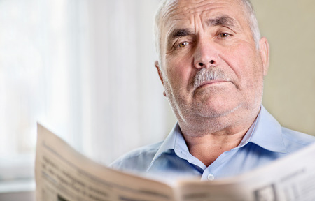 quizzical: Senior man relaxing reading a newspaper looking up with a frown and quizzical expression at the camera