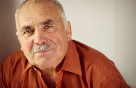 Friendly senior man with a moustache leaning forwards as he looks at the camera with a quiet smile, copyspace on a grey background Stock Photo