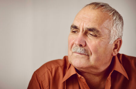 dignity: Thoughtful senior man with a moustache sitting reminiscing staring down at the ground with a serious contemplative expression Stock Photo