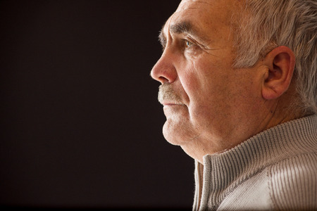 introspective: Beautiful portrait of a pensive senior man with a moustache in profile on a black background with copyspace staring straight ahead as he reminisces on his life Stock Photo