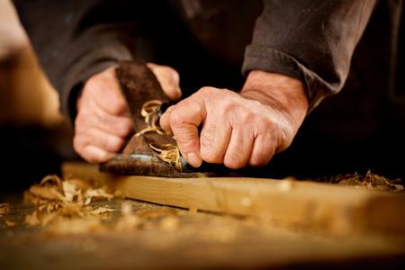 Senior man of timmerman doet houtbewerking schaven het oppervlak van een houten plank in zijn werkplaats met een manuele vliegtuig als hij geniet van zijn creatieve hobby