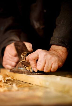 Senior Mann oder Tischler tun Holzbearbeitung Hobeln der Oberfläche einer Holzplanke in seiner Werkstatt mit einer manuellen Ebene wie er sein kreatives Hobby genießt
