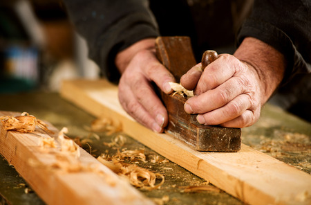 leveling: Skilled carpenter using a handheld plane to smooth and level the surface of a plank of hardwood, close up view of his hands, the tool and wood shavings Stock Photo