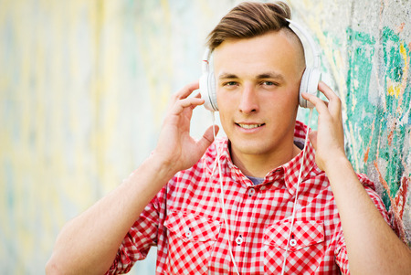 concentrates: Young man with a modern hairstyle listening to music on his earphones smiling as he concentrates on the tunes