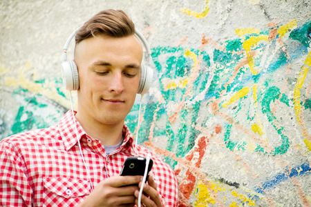downloaded: Hip young man listening to music downloaded on his MP3 player standing wearing a set of headphones in front of a grungy graffiti covered wall Stock Photo