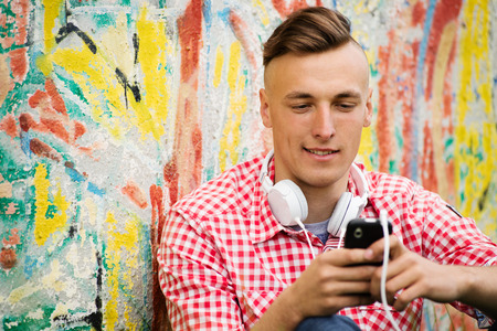 downloaded: Young man standing against a grungy exterior wall with graffiti searching through his downloaded music on his MP3 player for a favorite tune Stock Photo