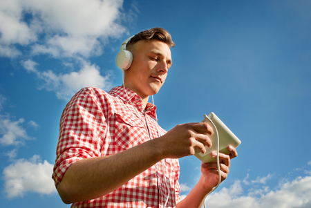 listening device: Low angle view against blue sky of a young man listening to music on his MP3 player standing searching through his library of tunes while listening on his headphones