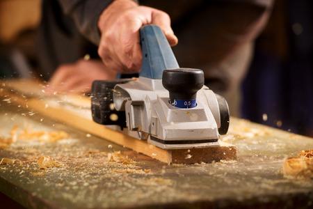 Nahaufnahme von der Hand eines älteren Mannes Hobeln ein Brett aus Holz in seiner Schreinerwerkstatt mit einem Flugzeug, um die Oberfläche zu glätten Lizenzfreie Bilder