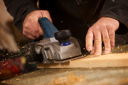 carpenter's sawdust: Close up of the hand of an elderly man planing a plank of wood in his carpentry workshop with a plane to smooth the surface Stock Photo