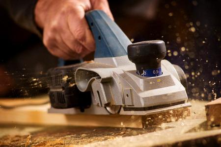 老人の飛行機で彼の大工のワーク ショップで木の板を削り、表面を滑らかにする手のクローズ アップ