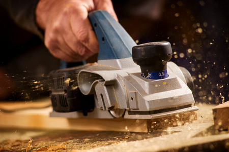sanding: Close up of the hand of an elderly man planing a plank of wood in his carpentry workshop with a plane to smooth the surface Stock Photo