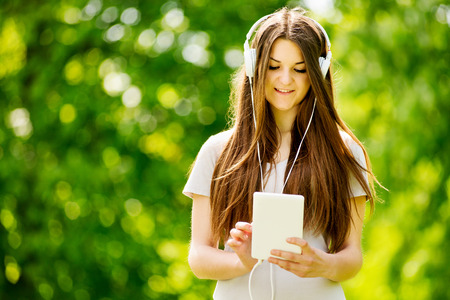 downloaded: Pretty teenage girl listening to music on her earphones selecting a downloaded tune off her tablet or MP3 player with a smile of anticipation as she stands in a leafy garden Stock Photo