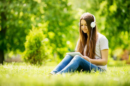listening device: Young woman listening to music in a lush park sitting on the grass with her tablet on her knees selecting a tune to listen to on her headphones