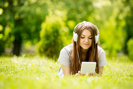 downloaded: Young woman lying on the grass listening to music on her headphones that she has downloaded onto her tablet or MP3 player as she enjoys the tranquility of a lush green park Stock Photo