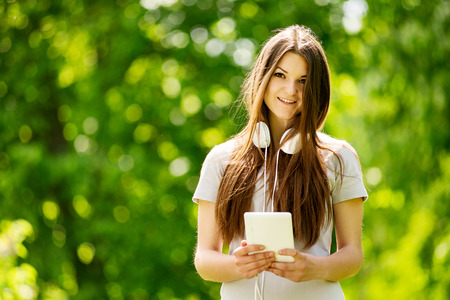 downloaded: Beautiful young woman listening to music standing smiling at the camera with her headphones around her neck as she searches her tablet for a downloaded tune