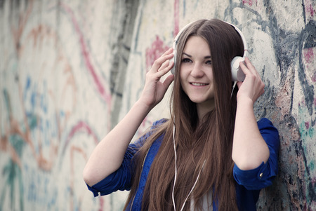 Smiling young teenager listening to music on a set of headphones as she stands against a grunge graffiti covered urban wall with copyspace